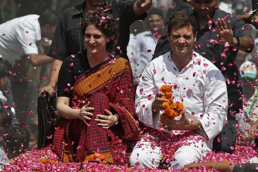 Rahul Gandhi (in white), India's ruling Congress Party vice-president and son of Congress chief Sonia Gandhi, and his sister Priyanka Gandhi Vadra are showered with rose petals by their supporters upon Rahul's arrival to file his nomination for the g