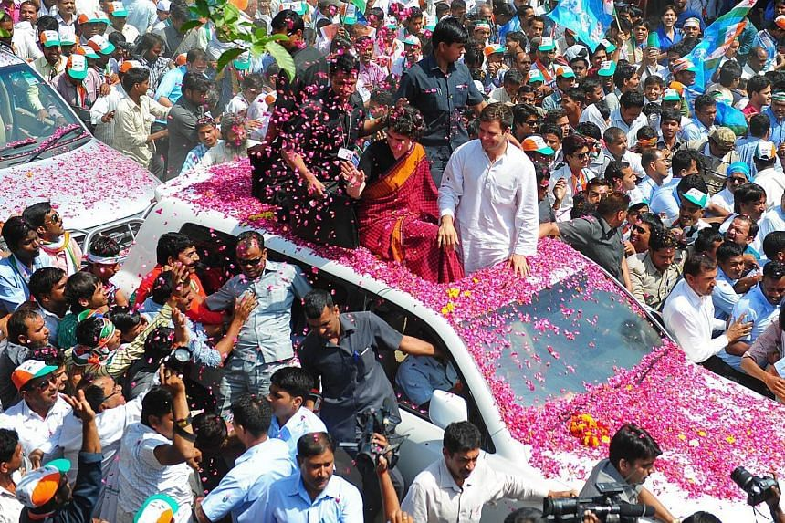 Indian Congress Party vice-president Rahul Gandhi and his sister Priyanka Gandhi (centre) are showered with flower petals by supporters as they ride on top of a car before Rahul filed his nomination for the upcoming Lok Sabha (Lower House) elections