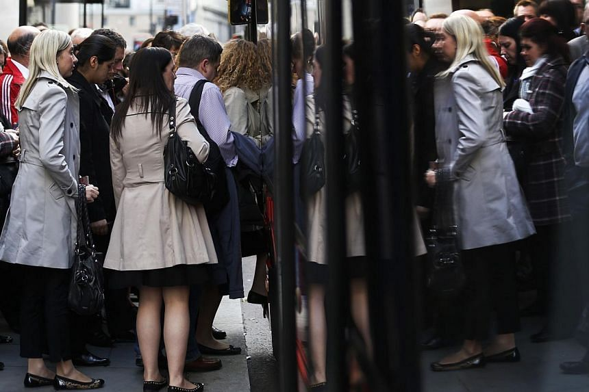 People board a bus from a busy bus-stop during rush hour outside Liverpool Street station in London on April 28, 2014. -- PHOTO: REUTERS