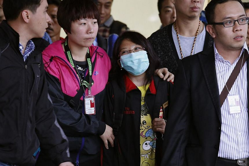 Indonesian domestic helper Erwiana Sulistyaningsih (centre), accompanied by Hong Kong Airport Authority personnel, police and representatives from the Indonesian Consulate, walks out from a special exit upon her arrival at the Hong Kong Airport, on A