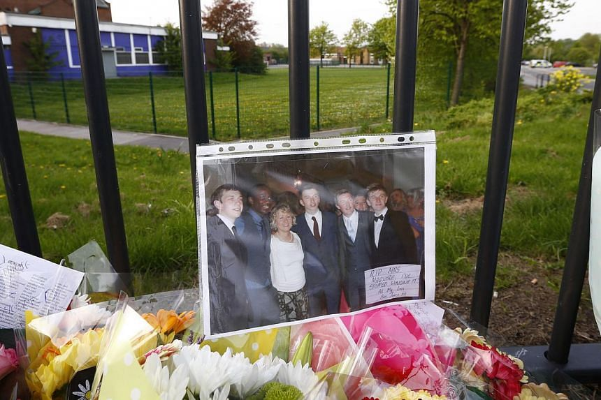 A photograph of teacher Anne Maguire (third from left) sits on floral tributes outside Corpus Christi Catholic College after she was fatally stabbed in Leeds, northern England on April 28, 2014. -- PHOTO: REUTERS