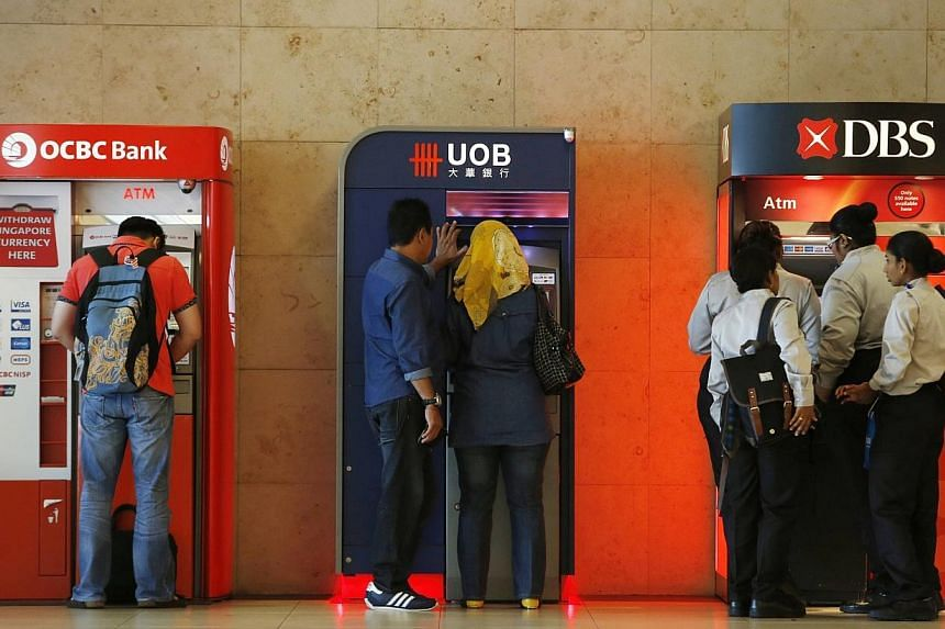 People using United Overseas Bank (UOB), Development Bank of Singapore (DBS) and Oversea-Chinese Banking Corp (OCBC) automated teller machines at the airport in Singapore April 30, 2014.Bank lending grew at a slightly faster pace last month, af