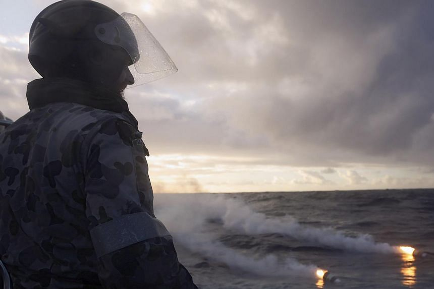A seaman observes markers dropped from a Royal New Zealand Air Force (RNZAF) P3K Orion after an object was sighted in the southern Indian Ocean during the continuing search for the missing Malaysian Airlines flight MH370 on April 17, 2014. -- FILE PH