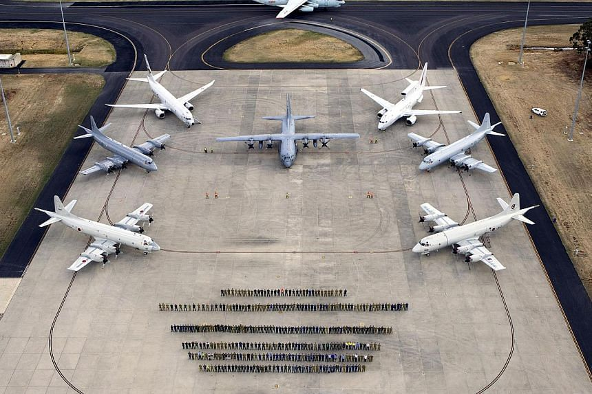 International and Royal Australian Air Force (RAAF) air crews and officials who participated in the search for missing Malaysia Airlines plane MH370 pose for a photograph on the tarmac at the RAAF Base Pearce, located north of Perth, on April 29, 201