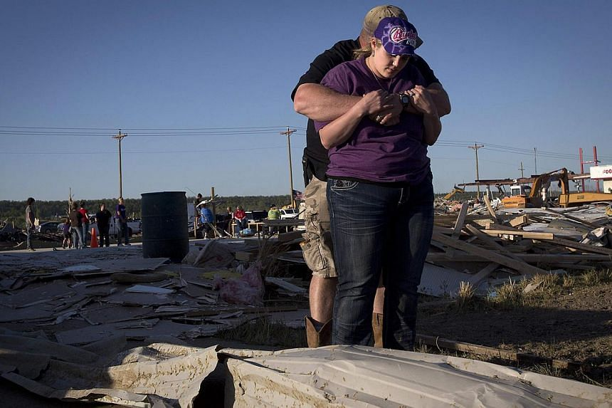 Shane and wife Alexis Cauthen of The Valley Church hug after they were cleaning up what was their chapel in Vilonia, Arkansas April 29, 2014. The Cauthens lost their house and most of the possessions in the storm. The church was leveled and they plan