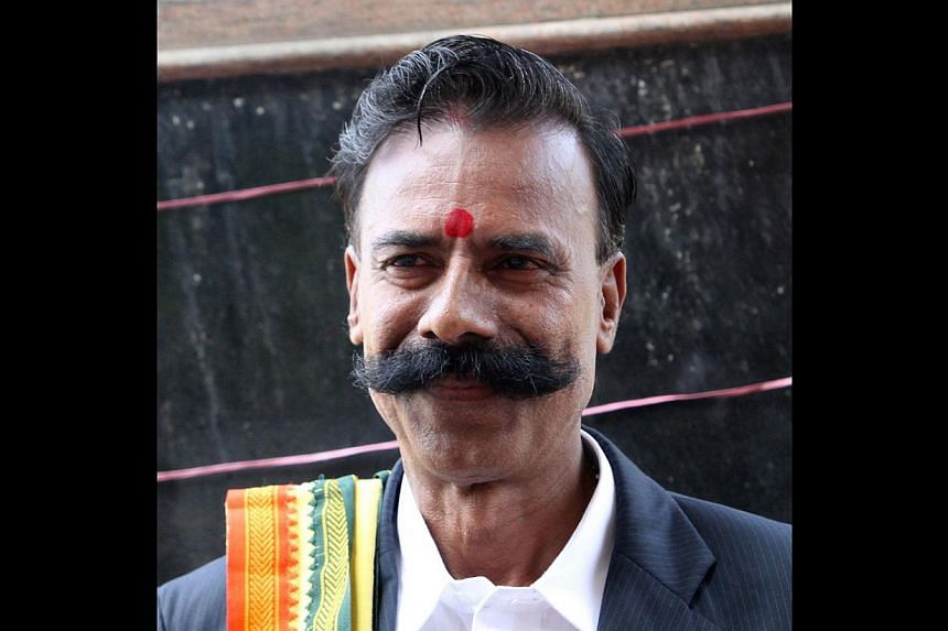 In this photograph taken on September 11, 2013, Indian shop owner K. Padmarajan poses during campaigning in Vadodra in the western state of Gujarat. Indian shop owner K. Padmarajan doesn't feel like a loser. In fact, he sees much to celebrate in the
