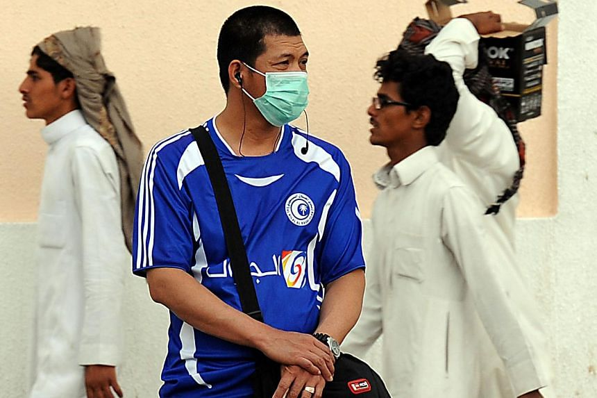 A foreign worker living in Riyadh wears a mask covering his mouth and nose on a main street in the Saudi capital on April 29, 2014 as the death toll from the newly emerged and often fatal Middle East Respiratory Syndrome (MERS) disease topped 100 in
