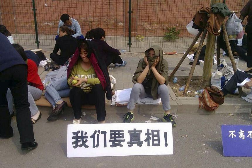 """Family members of passengers aboard the missing Malaysia Airlines flight MH370 gather during a sit-in protest outside the Malaysian embassy in Beijing on April 25, 2014. The sign in white reads: """"We want the truth.""""-- FILE PHOTO: REUTERS"""