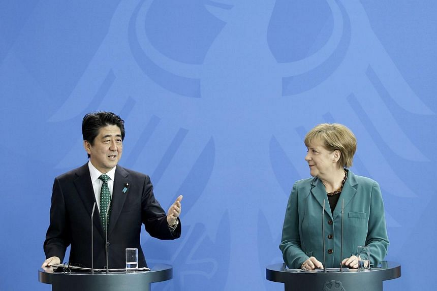 German Chancellor Angela Merkel and Japan's Prime Minister Shinzo Abe attend a news conference after their meeting at the Chancellery in Berlin, on April 30, 2014. Mr Abe, on a visit to Germany on Wednesday, called for swift progress in talks with th