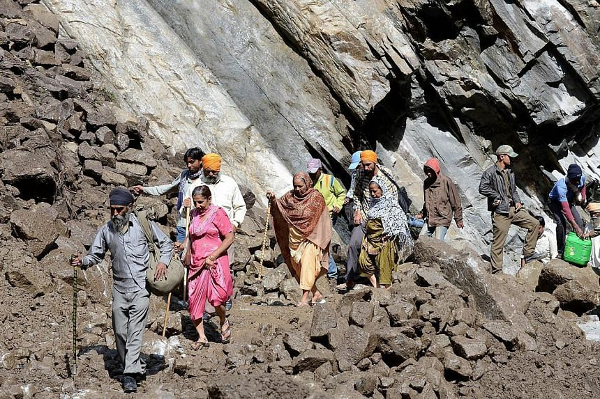 Indian Hindu pilgrims and villagers make their way across a landslide caused by overnight rains as they walk through Govindghat following flash floods in northern Uttarakhand state, on June 30, 2013. Hydropower projects in northern India were partly