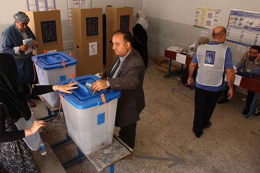 Iraqi Kurdish residents mark their ballots at voting booths inside a polling station during parliamentary election, in the northern Iraqi province of Dohuk, on April 30, 2014. Voters braved the threat of attacks to stream to polling centres Wednesday