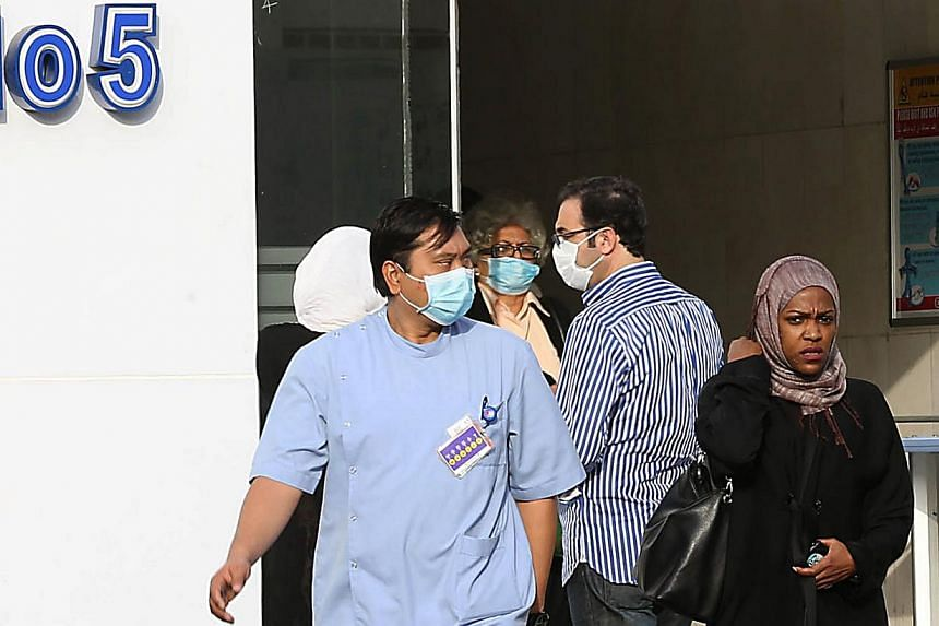 Medical workers and foreigners wear a mouth and nose mask as they leave a local hospital's emergency department, on April 22, 2014, in the Red Sea coastal city of Jeddah. Saudi health authorities announced on Wednesday, April 30, 2014, two new deaths