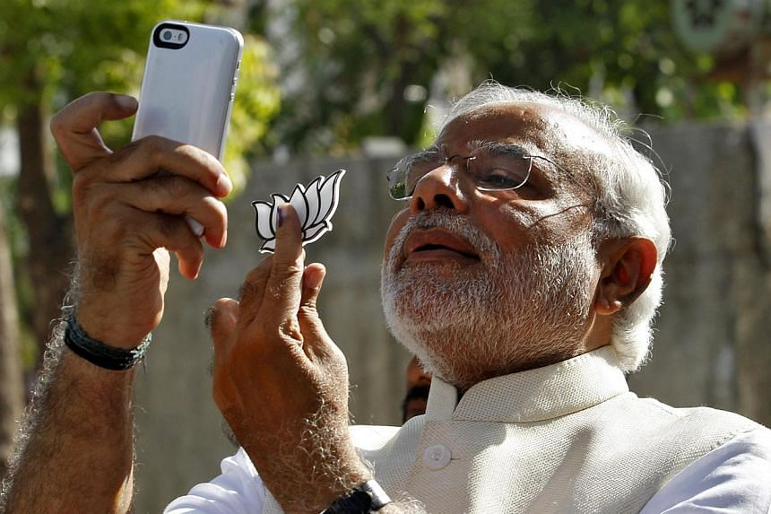 """Hindu nationalist Narendra Modi, the prime ministerial candidate for India's main opposition Bharatiya Janata Party (BJP), takes a """"selfie"""" with a mobile phone after casting his vote at a polling station during the seventh phase of India's general el"""