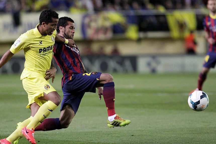 Barcelona's Dani Alves and Villarreal's Giovani Dos Santos fight for the ball during their Spanish first division soccer match at the Madrigal stadium in Villarreal, on April 27, 2014. Spanish police have detained the Villarreal supporter who threw a