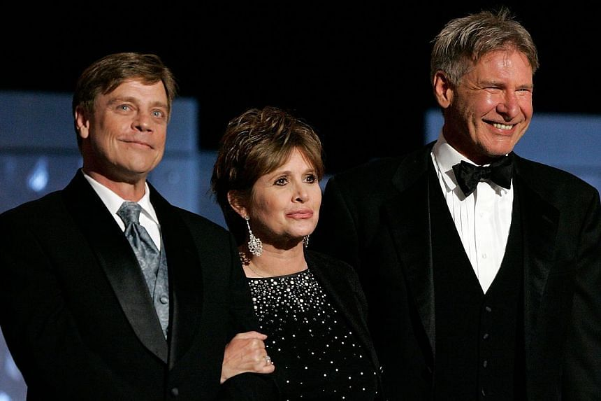 Actors (from left) Mark Hamill, Carrie Fisher and Harrison Ford onstage during the 33rd AFI Life Achievement Award tribute to George Lucas at the Kodak Theatre in Hollywood, California, on June 9, 2005. -- FILE PHOTO: AFP