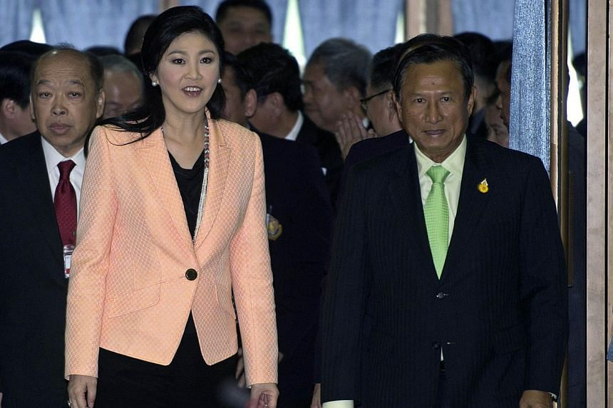 Thai Prime Minister Yingluck Shinawatra (left) walks with Thai Election Commission (EC) Chairman Supachai Somcharoen (right) during the meeting to discuss a future election at the Thai Air Force Academy in Bangkok, on April 30, 2014. Thailand's prime