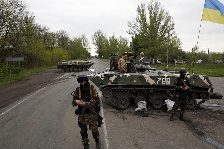 """Ukrainian soldiers stand guard in front of armoured personnel carriers at a check point near the village of Malinivka, southeast of Slaviansk, in eastern Ukraine, on April 29, 2014. Ukraine's military is """"on full combat alert"""" against a possible inva"""