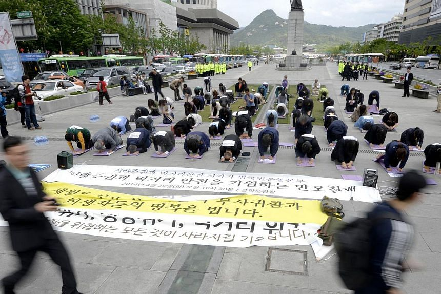 People bow in memory of the victims of the sunken passenger ship Sewol in central Seoul on April 29, 2014. -- PHOTO: REUTERS
