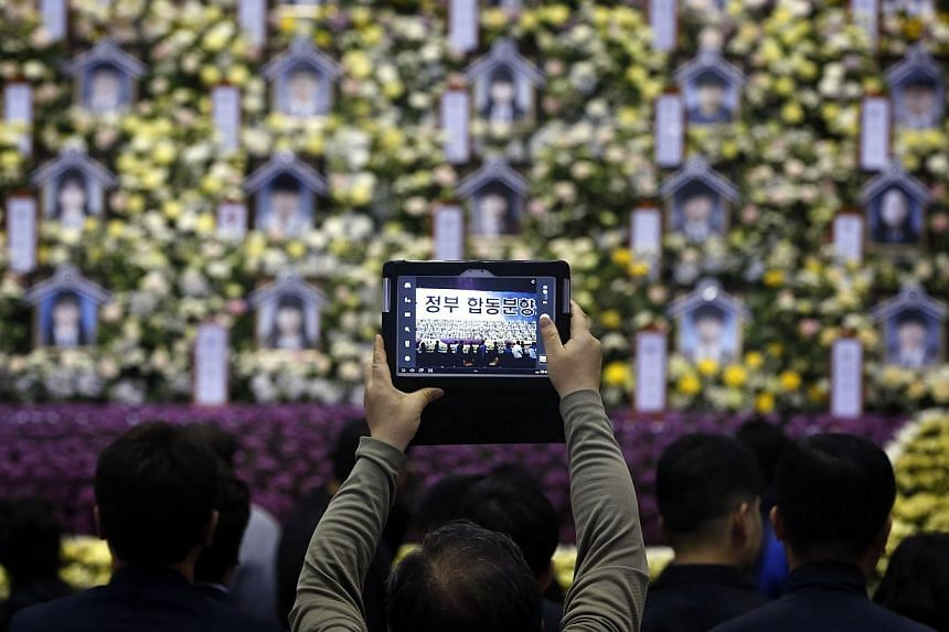 A mourner takes a photo at the official memorial altar for victims of the sunken passenger ship Sewol, in Ansan on April 30, 2014. -- PHOTO: REUTERS