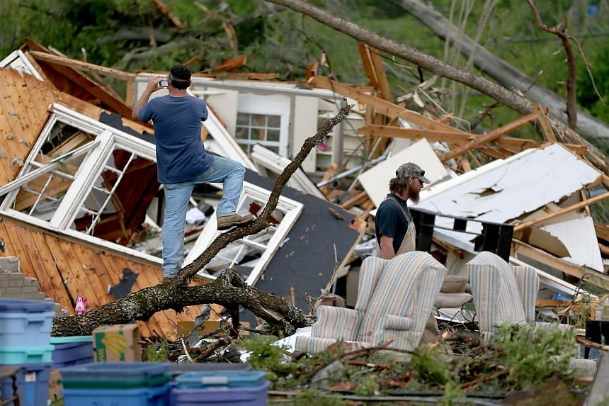 Kevin Melton (left) and Larry Lamb look at a home that was destroyed by a tornado in Tupelo, Mississippi on April 29, 2014. -- PHOTO: AFP