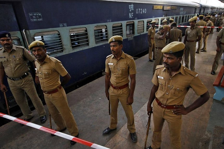 Indian policemen stand guard next to a passenger train in which two explosions occurred, at the railway station in the southern Indian city of Chennai on May 1, 2014.Two bombs went off on a train in the southern Indian city of Chennai on Thursd