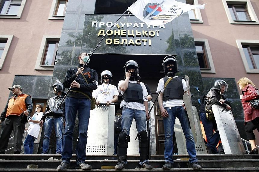 Pro-Russian activists stand outside the prosecutor's office in Donetsk on May 1, 2014.A crowd of some 300 pro-Russian militants hurling rocks and Molotov cocktails seized control of the prosecutor's office in the eastern Ukrainian city of Donet