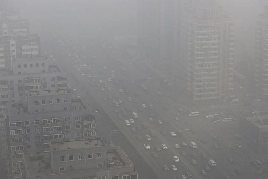 Cars drive on the Three Ring Road amid the heavy haze in Beijing February 26, 2014.A Beijing man is seeking to divorce his wife after she took their son to a tropical island province to escape the capital's notorious smog, saying the long-dista
