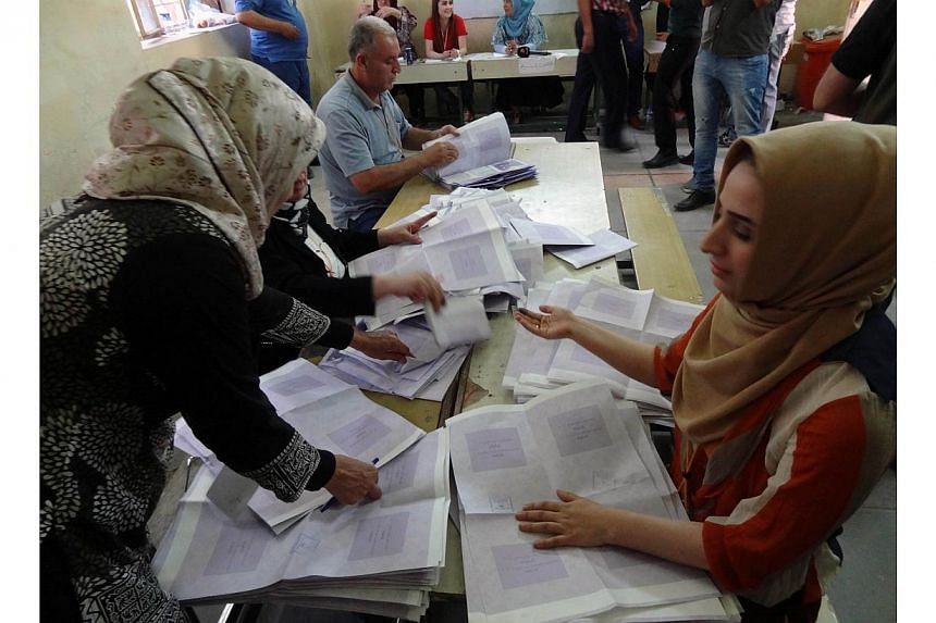 Election commission officials count votes at the Khabat polling station north of the Iraqi city of Kirkuk on April 30, 2014.Vote counting is under way on Thursday following Iraq's relatively peaceful elections, but with results not due fo
