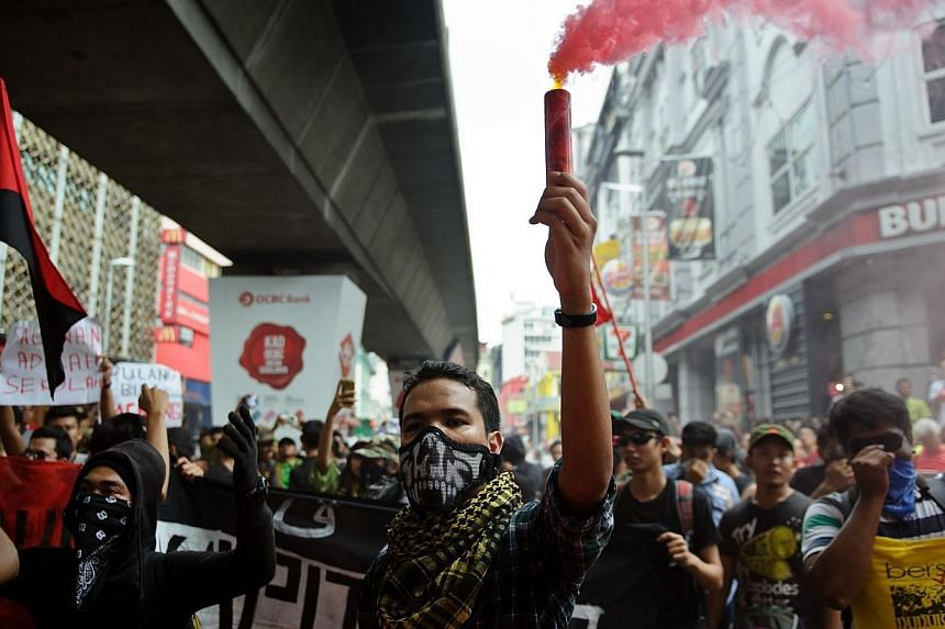 A protester holds a flare during a May Day protest in Kuala Lumpur on May 1, 2014. Thousands have gathered in downtown Kuala Lumpur to protest against the Goods-and-Services Tax (GST) to be introduced next year. -- PHOTO: AFP