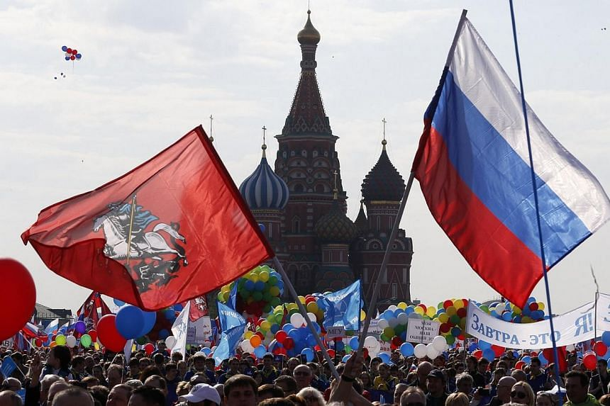 People walk through Red Square with flags and banners during a rally in Moscow May 1, 2014. Some 100,000 workers on Thursday paraded on Red Square for the first time since the 1991 Soviet break-up as the takeover of Crimea triggered a surge of patrio