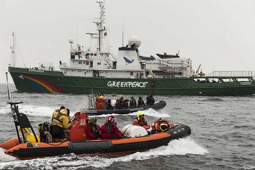 Greenpeace members speed up in a rubber speedboat while waiting for the Russian oil tanker Mikhail Ulyanov off the coast of the Hague April 30, 2014.The Dutch police on Thursday boarded a Greenpeace ship in Rotterdam harbour as it tried to stop