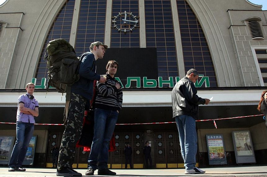 People wait outside the Kiev-Passenger Railway Station in Kiev on April 30, 2014, closed due information about a possible threat in the station involving mines. ussia's military attache to Kiev has been detained on suspicion of espionage and ord