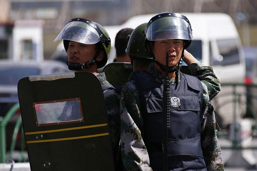 Paramilitary policemen stand guard outside the South Railway Station, where three people were killed and 79 wounded in a bomb and knife attack on Wednesday, in Urumqi, Xinjiang Uighur Autonomous region, May 1, 2014.The three people who died in