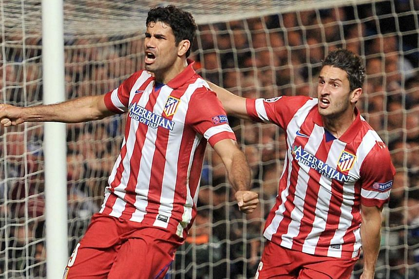 Atletico Madrid's Brazilian-born forward Diego da Silva Costa (left) celebrates scoring his team's second goal with Spanish midfielder Koke during the Uefa Champions League semi-final second leg football match between Chelsea and Atletico Madrid at S