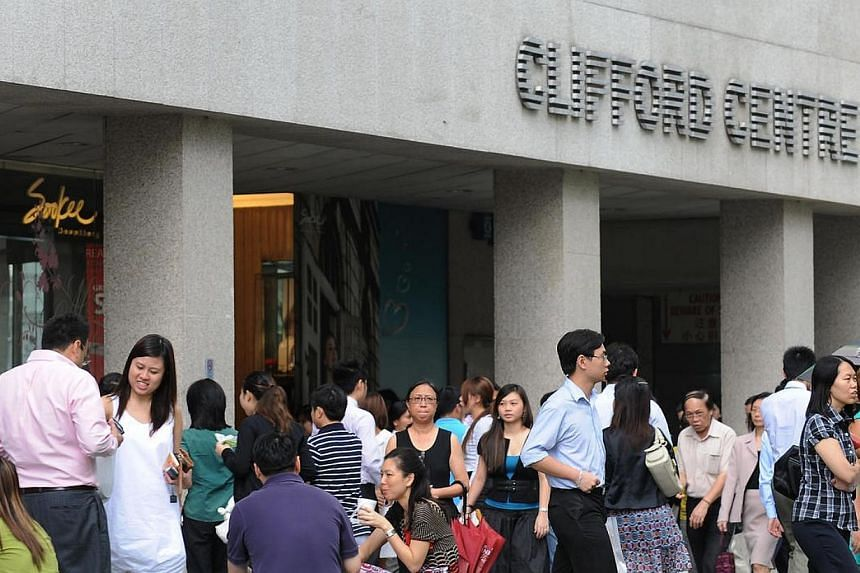 Office workers at Clifford Centre, Raffles Place, during lunch hour.Opposition parties in Singapore urged relooks at national labour policies in their May Day messages posted online. -- ST FILE PHOTO:JOYCE FANG