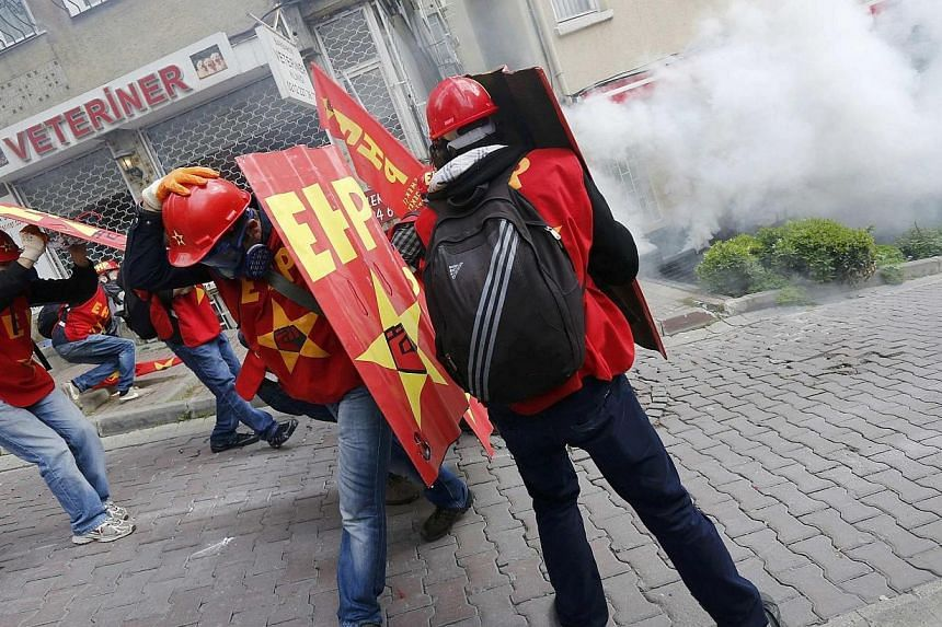 Protesters shield themselves from tear gas fired by riot police during a May Day demonstration in Istanbul on May 1, 2014. Turkish police fired water cannon and tear gas to prevent hundreds of protesters from defying a ban on May Day rallies and reac