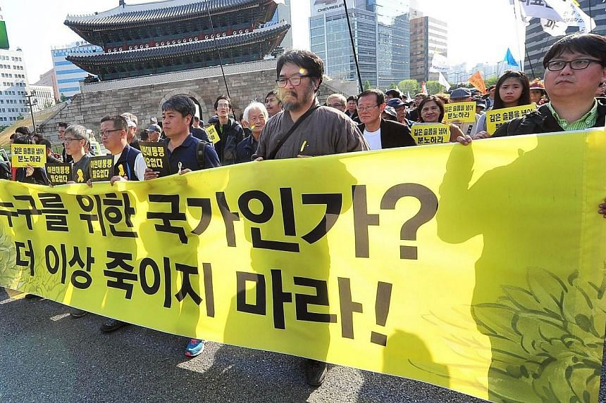 """South Korean workers march with a big banner reading """"What does this country work for? Do not kill people any more"""" during a May Day rally in Seoul on May 1, 2014. -- PHOTO: AFP"""
