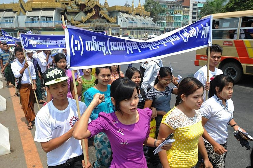 Protesters shout slogans and display placards during a May Day rally in Yangon on May 1, 2014. -- PHOTO: AFP
