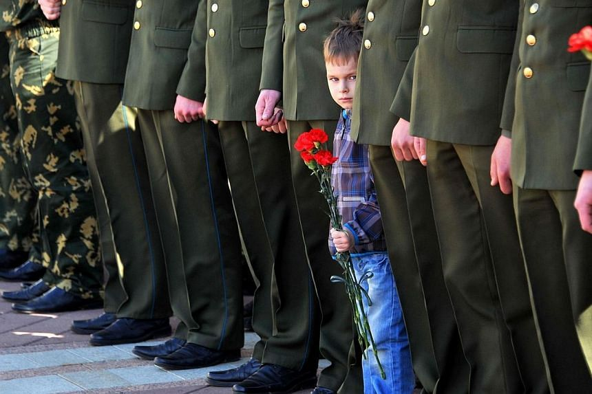A little boy holds flowers near the honour guard as members of Belarus Communist Party lay flowers at a monument to Soviet Union founder Vladimir Lenin to mark the May Day in central Minsk, on May 1, 2014. -- PHOTO: AFP