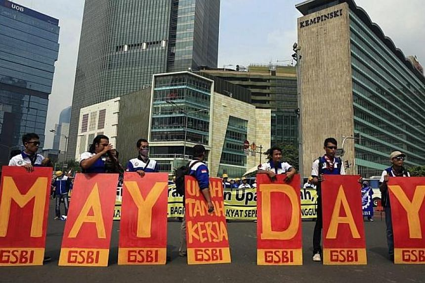 Indonesian Workers' Unions (KSPI) members hold placards during a May Day rally at the business district in Jakarta on May 1, 2014. -- PHOTO: REUTERS