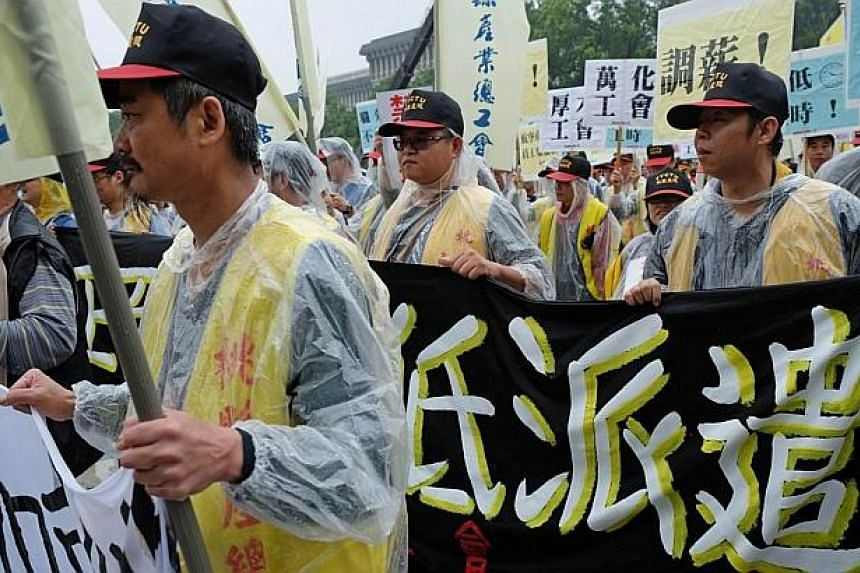 """Protesters display a banner reading """"oppose the dispatch workers"""" during a May Day rally in Taipei on May 1, 2014. -- PHOTO: AFP"""