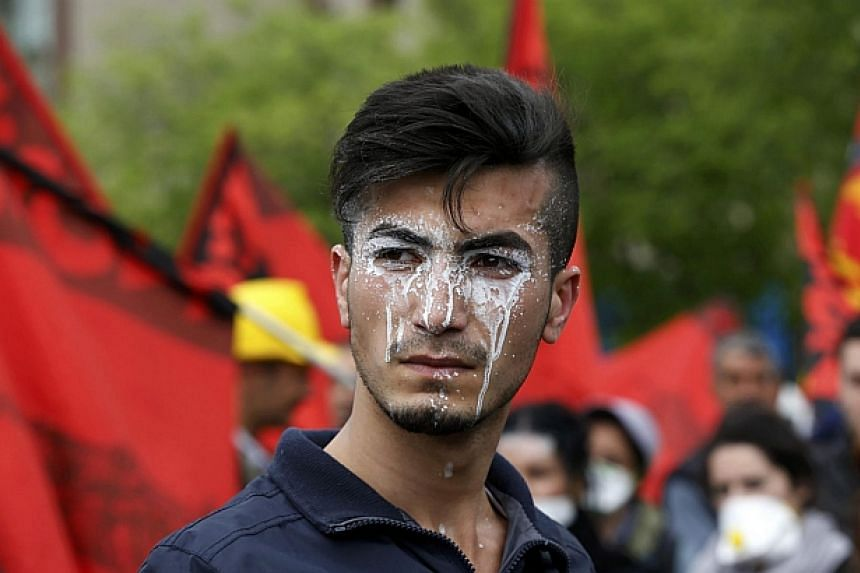 A protester, with cream applied to his face to protect against tear gas, reacts during a May Day demonstration in Istanbul on May 1, 2014. -- PHOTO: REUTERS