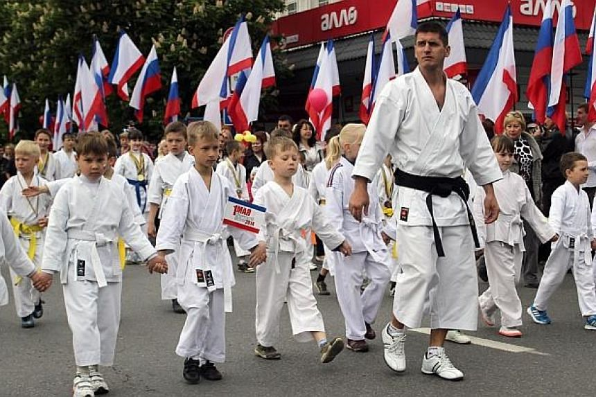 Young students of Martial Arts parade past Russian and Crimean flags during a rally to mark May Day in central Simferopol, the capital of Crimea on May 1, 2014. -- PHOTO: AFP