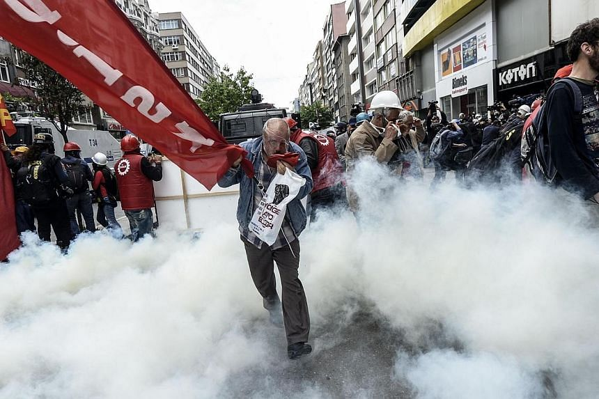 Turkish protesters run for cover as riot police fire tear gas to disperse a May Day rally near Taksim Square in Istanbul on May 1, 2014. -- PHOTO: AFP