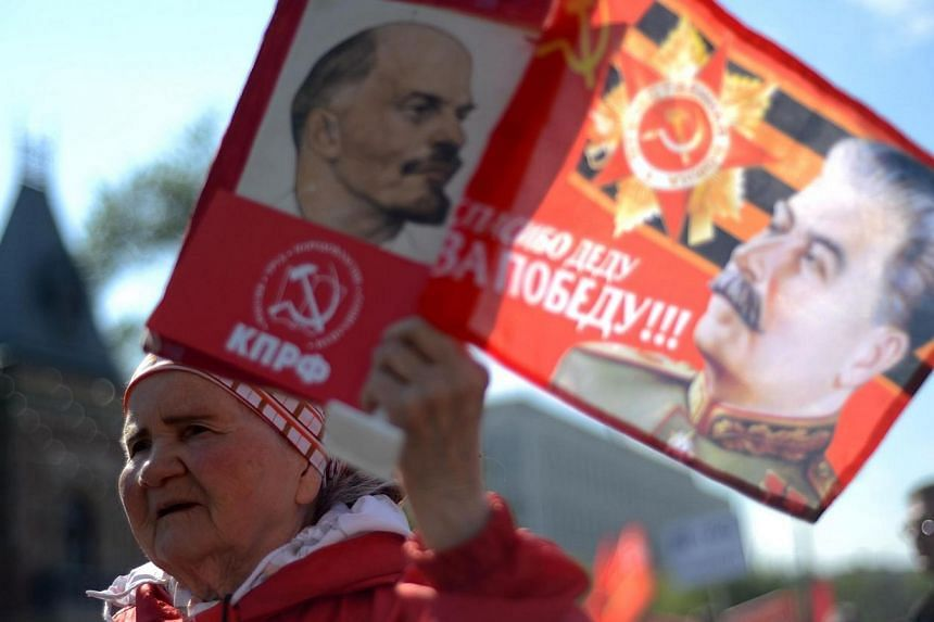 An elderly Russian Communist Party activist carries portraits of the Soviet Union's founder Vladimir Lenin (left) and Soviet dictator Josef Stalin during a traditional May Day rally in central Moscow on May 1, 2014. -- PHOTO: AFP