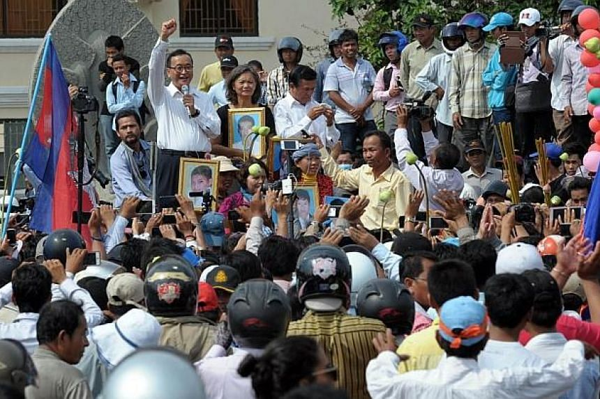 Leader of the opposition Cambodia National Rescue Party (CNRP) Sam Rainsy (top left) speaks to supporters during a rally in Phnom Penh on May 1, 2014. -- PHOTO: AFP