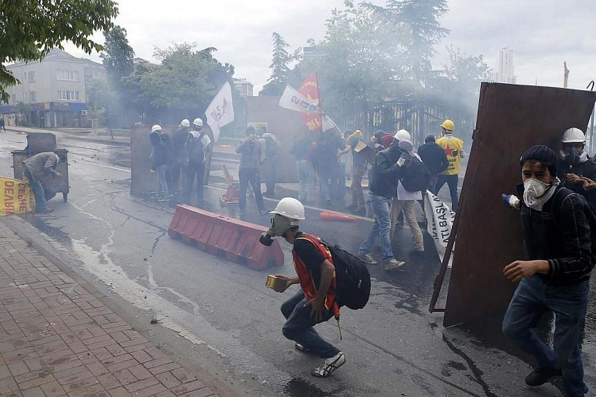 Protesters shield themselves from tear gas fired by riot police during a May Day demonstration in Istanbul on May 1, 2014. -- PHOTO: REUTERS