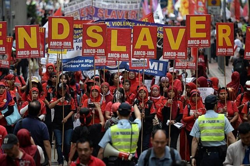 """Migrant workers from Indonesia carry placards which collectively read """"End Slavery"""" (top) during a Labour Day rally in Hong Kong on May 1, 2014. -- PHOTO: AFP"""