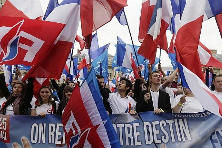 Supporters of France's far-right National Front (FN) wave French and FN flags while holding a campaign banner for the upcoming European elections during a May Day rally in Paris on May 1, 2014. -- PHOTO: AFP