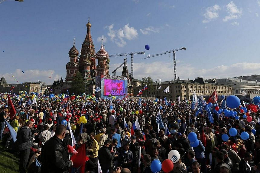 People walk with flags and banners towards St. Basil's Cathedral on Red Square during a rally in Moscow on May 1, 2014. -- PHOTO: REUTERS